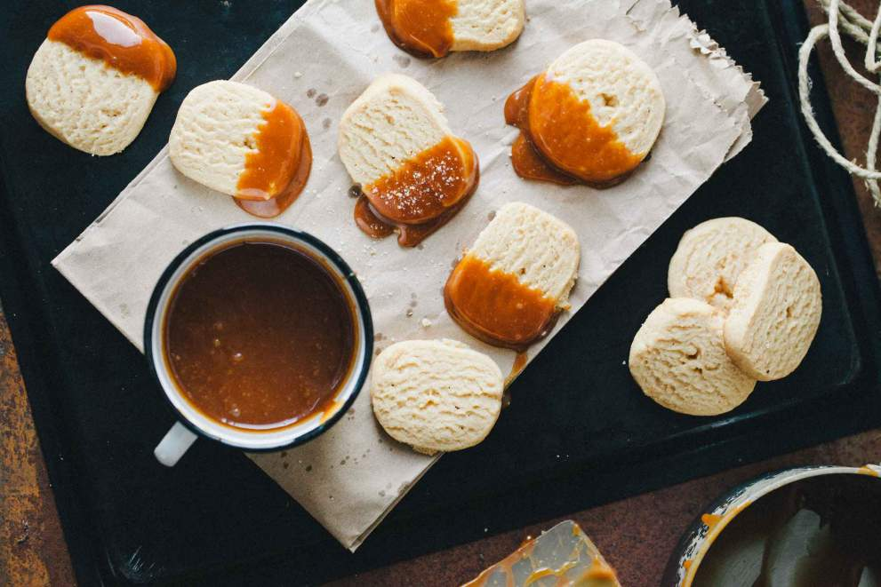Peanut butter cookies dipped in salty caramel on a tray