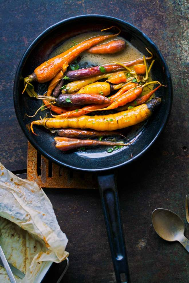 Braised carrots in a pan with herbs