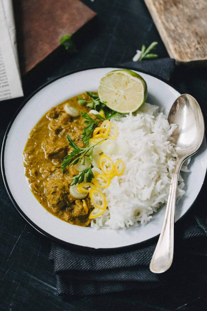 Chicken korma served with rice and coriander on the plate