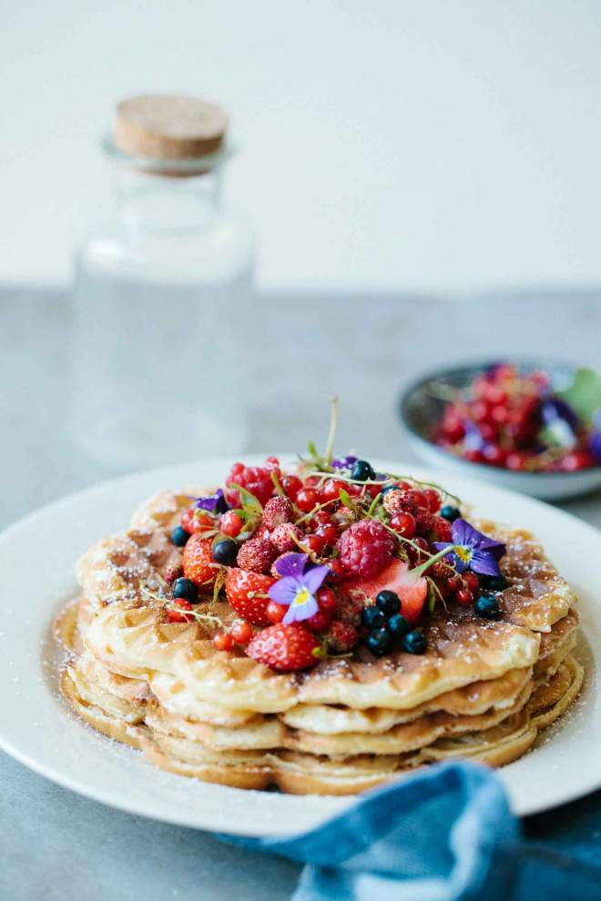 Crisp waffles served with berries and icing sugar