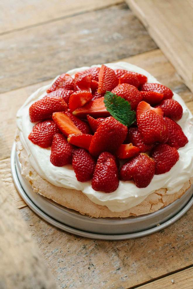 Pavlova with strawberries and cream served on a plate