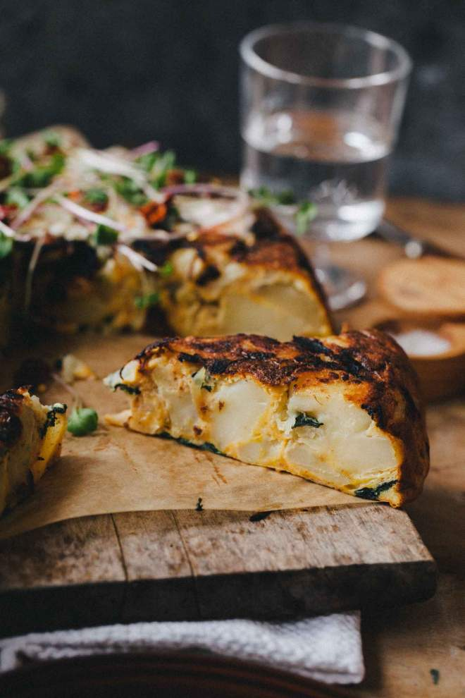 Tortilla de patatas cut on slices and served with herbs