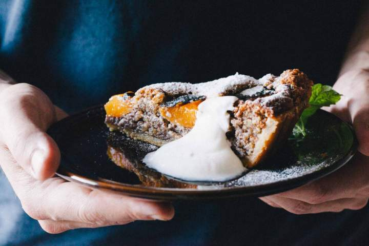 Slice of apricot tart with a dollop of greek yogurt