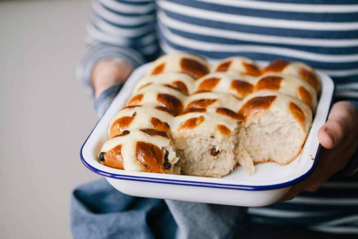 Baked hot cross buns in a baking dish held by Jernej
