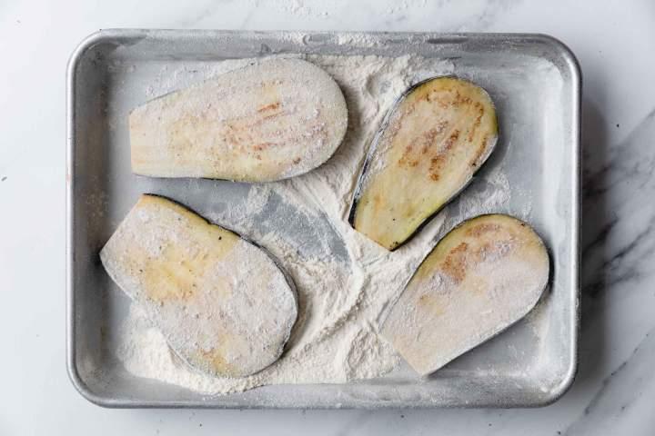 rolling eggplants in flour for Eggplant Parmesan (Melanzane alla Parmigiana)