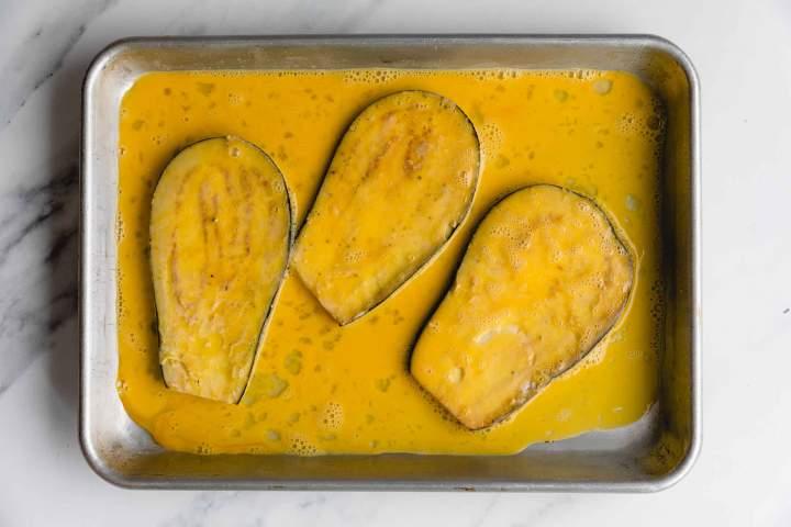dipping eggplants in eggwash for Eggplant Parmesan (Melanzane alla Parmigiana)