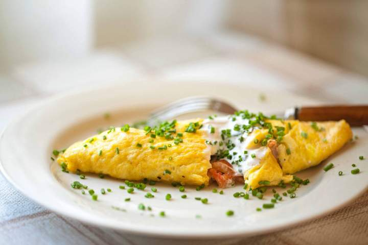 Omelette with Cherry Tomatoes on a Plate, served with sour cream and chives