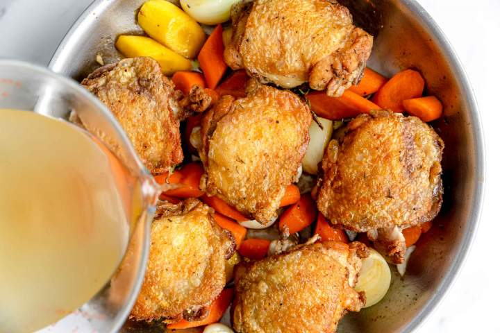 Adding chicken stock to chicken and vegetables for Oven-Baked Chicken Thighs with Carrots