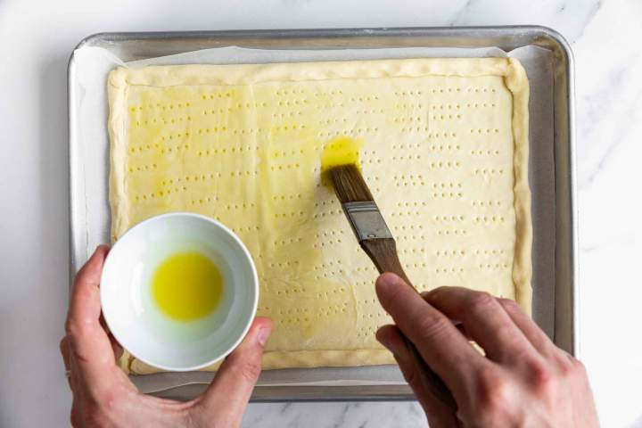 Brushing the puff pastry with olive oil for Puff Pastry Tomato Tart with Mozzarella