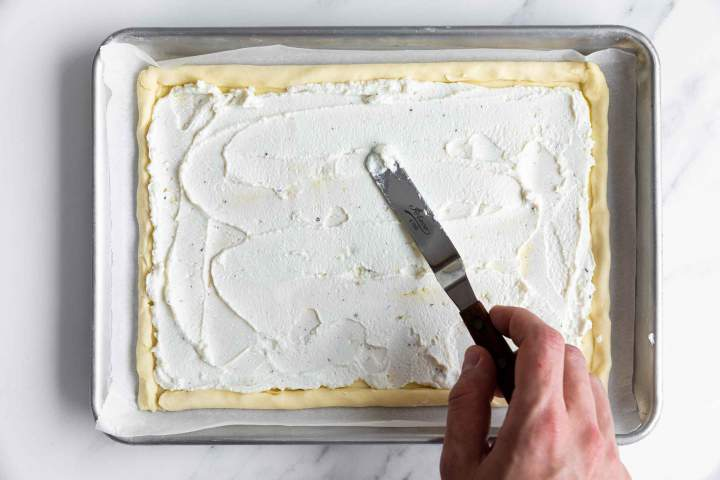 Spreading the ricotta filling on top of the puff pastry