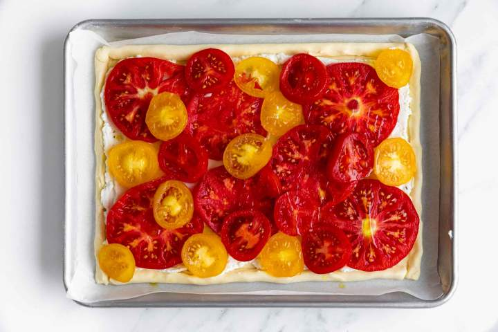 Arranging tomatoes on top of the ricotta filling