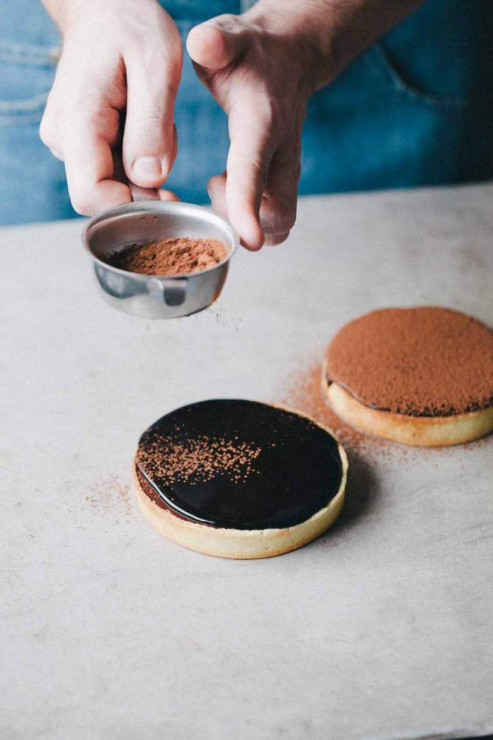 Dusting cacao over baked chocolate tarts with cacao glaze