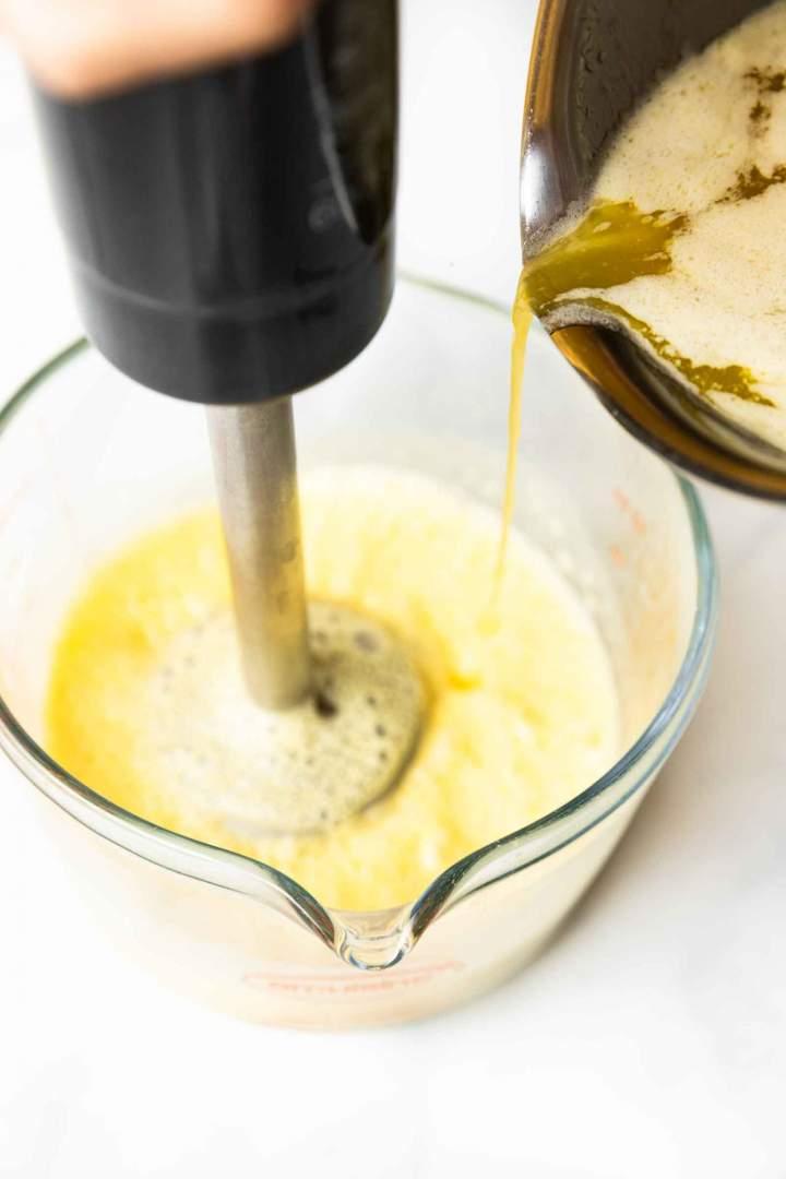 vlivanje vročega masla k jajcem za holandsko omako
