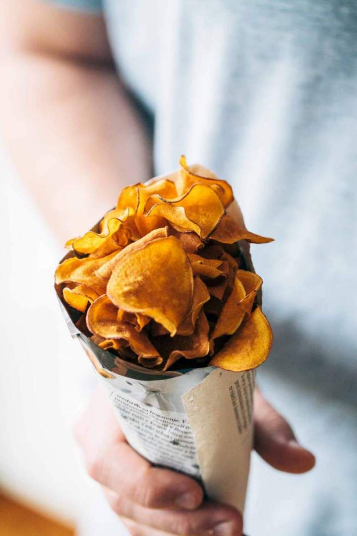 Sweet potato chips with rosemary salt in a paper bag