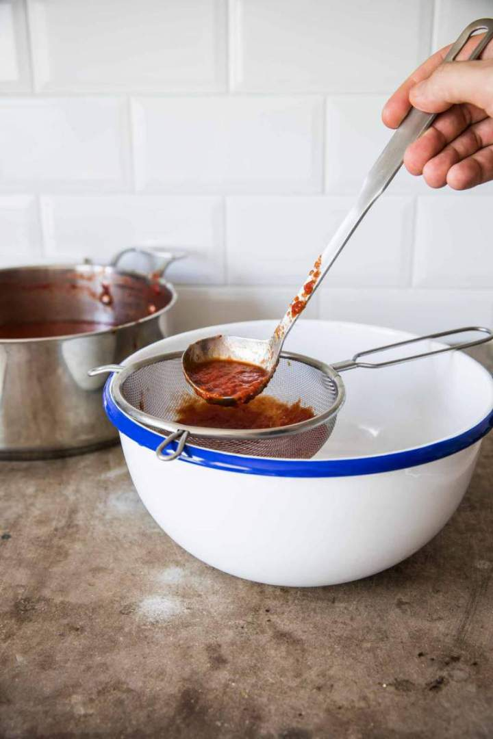 Straining Homemade Simple Tomato Purée through a sieve | jernejkitchen.com