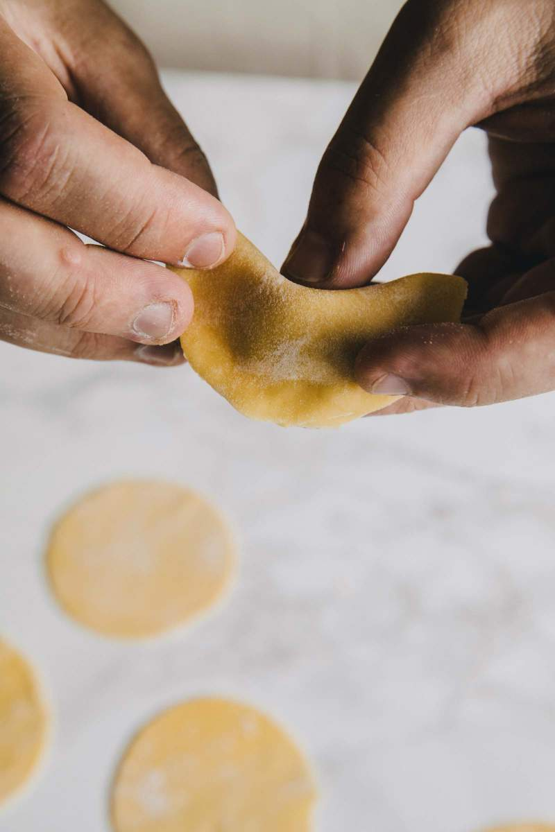 Shaping Tortellini stuffed with mortadella and lovage sauce