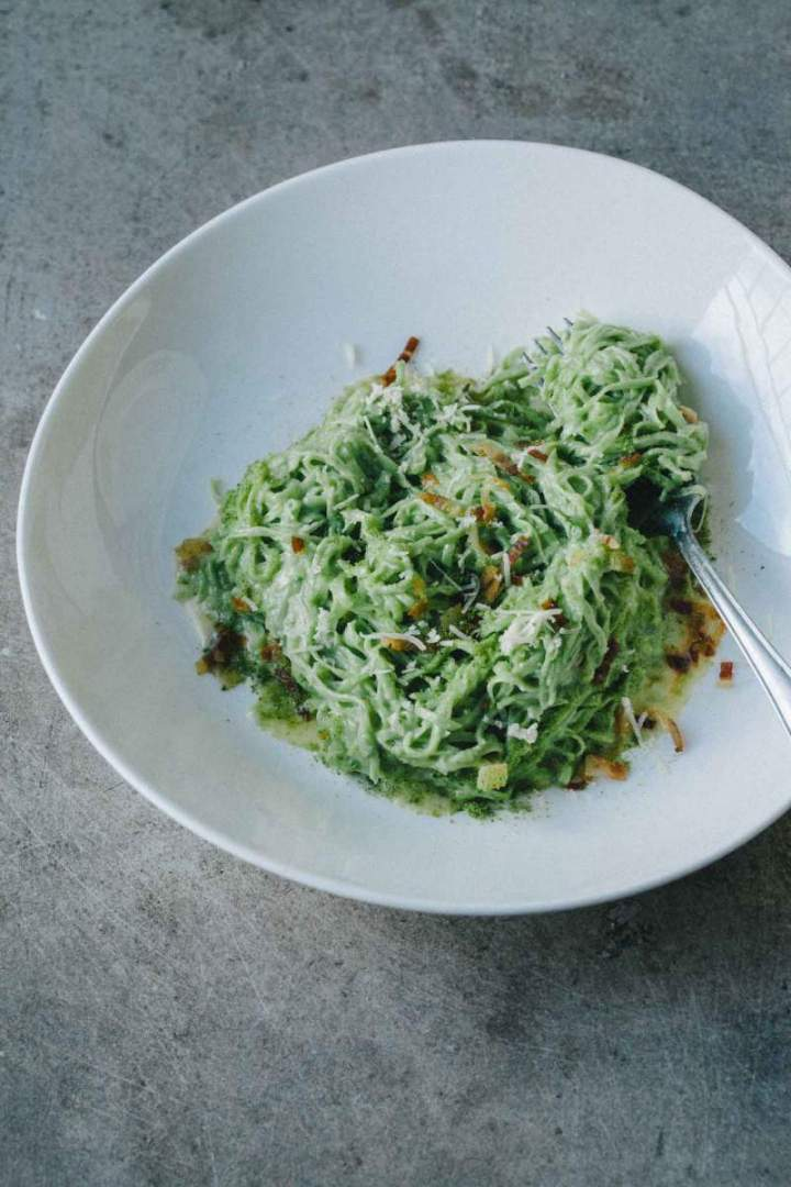 Wild garlic pasta with pancetta and green breadcrumbs served in a bowl